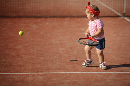 badminton: little funny girl plays tennis Stock Photo