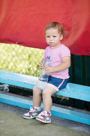 little girl with bottle of mineral water photo
