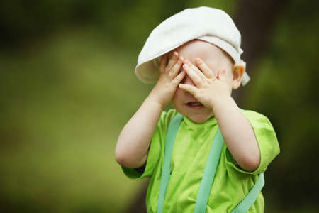 little funny boy plays hide and seek