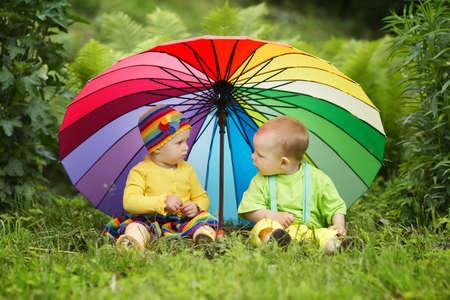 cute little children under colorful umbrella Archivio Fotografico