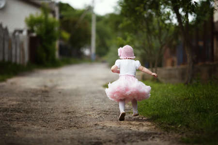 only 1 girl: cute little girl in dress running away Stock Photo
