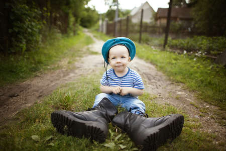 funny little boy in uniform on grass photo