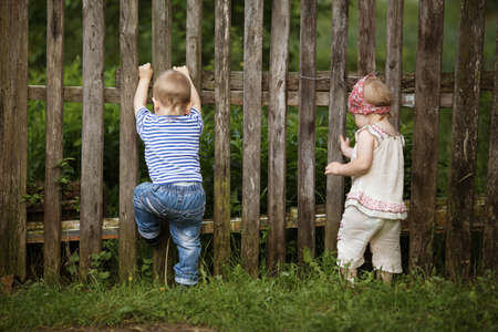 boy and girl climbing the fence photo