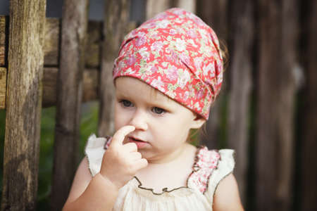 Cute little girl with finger in her nose photo