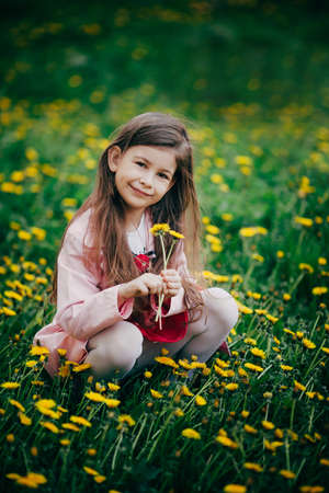 pretty small girl with long brown hair sitting in field of flowers photo