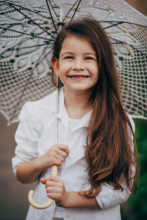 brunete: small and pretty  smiling girl with lace umbrella in white suit Stock Photo