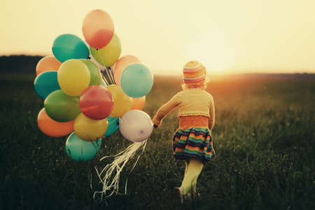children playing outside: little girl with colorful balloons