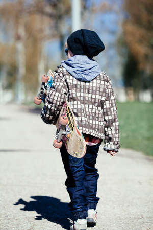 little funny boy with skateboard on the street photo