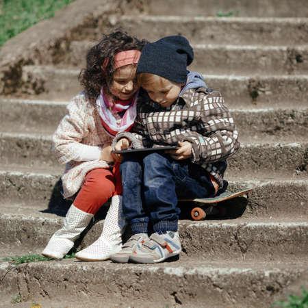 little modern boy and cute girl plaing on the street photo
