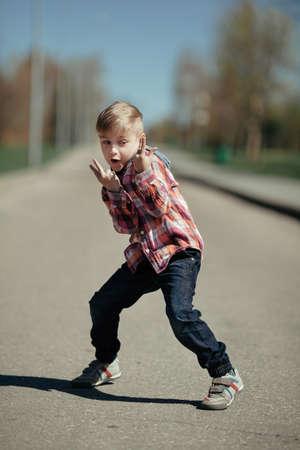 grimacing: little grimacing boy outdoors portrait Stock Photo