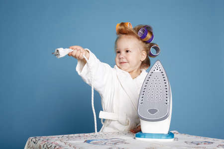 little housewife with iron on blue background photo