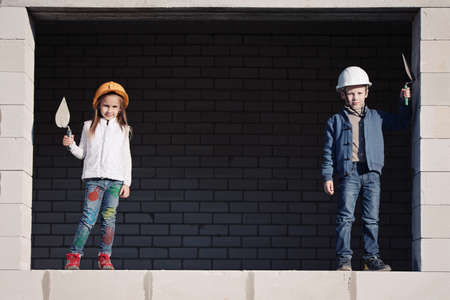 little boy and girl in helmets build house photo