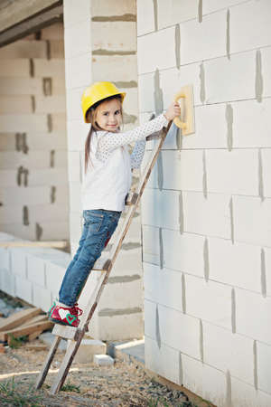little girl with helmet working on construction