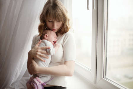 babies hands: mother with cute little crying baby Stock Photo