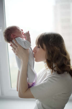 bacio: giovane madre con il bambino che piange Archivio Fotografico