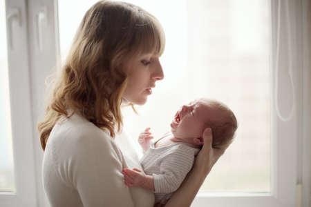nato: giovane madre con il bambino che piange Archivio Fotografico
