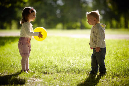 boy and girl playing with yellow ball Фото со стока