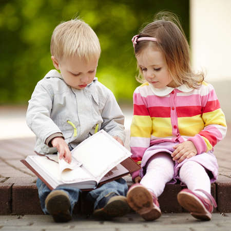 funny boy and girl reading book photo