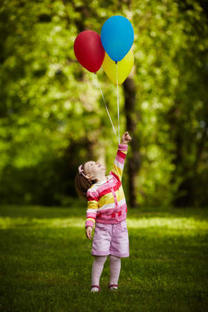 girl plays with balloons in park photo