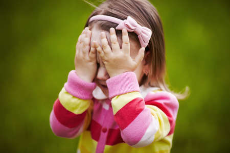 girl is playing hide-and-seek hiding face