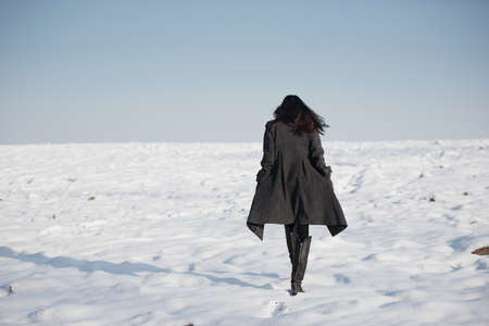 frozen lake: beautiful girl alone in winter field Stock Photo