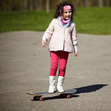 little girl skating on the street photo