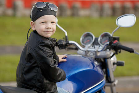 cute little biker on road with motorcycle Stock Photo