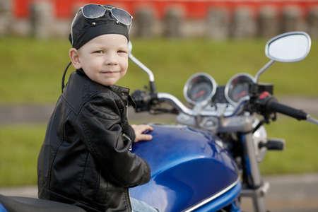 cute little biker on road with motorcycle Standard-Bild