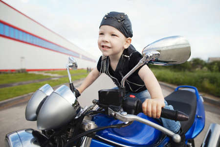 bike cover: cute little biker on road with motorcycle Stock Photo