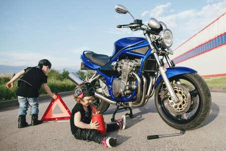cute little bikers repairs motorcycle on road photo