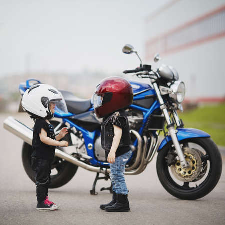 casco moto: lindos pequeños ciclistas en carretera con la motocicleta Foto de archivo