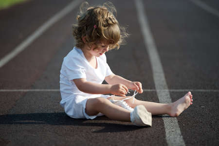 sweet beautiful little girl learning to tie shoelaces Standard-Bild
