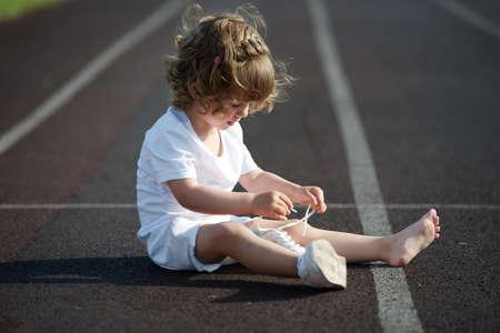 sweet beautiful little girl learning to tie shoelaces Standard-Bild