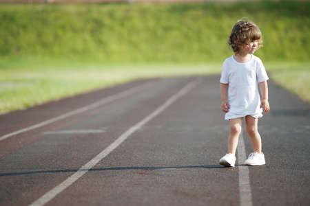 ittle: ittle cute girl running at stadium photo