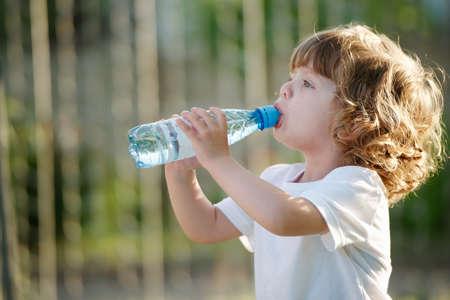 little beautiful girl drinking clean water from plastic bottle