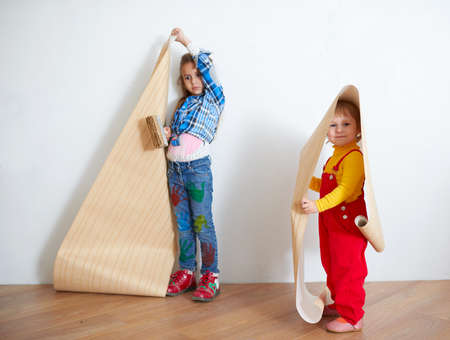 Cute little girls hanging wallpaper. Decorating the wall