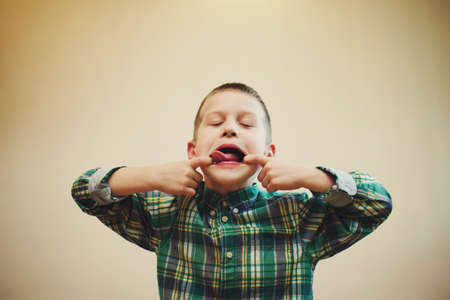 misbehaving: little funny boy shows tongue at home Stock Photo