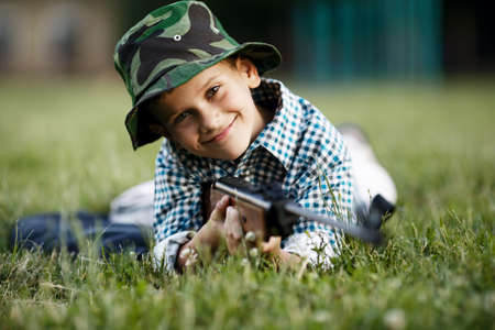 airgun: photo of little boy with airgun shooting outdoors
