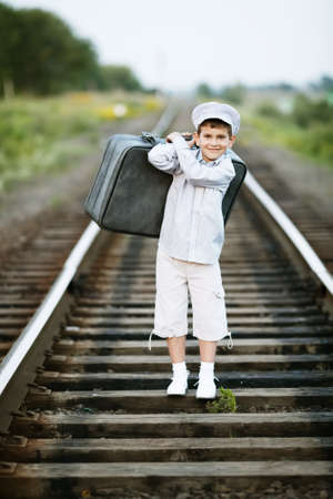 one child: photo of little boy with suitcase on railroad