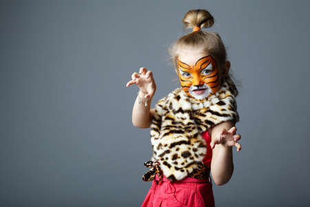 little funny girl with tiger costume on grey