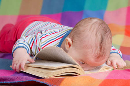 cute baby reading book on colorful background photo