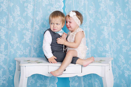 gemelos ni�o y ni�a: cute boy and girl sitting and crying with each other Foto de archivo