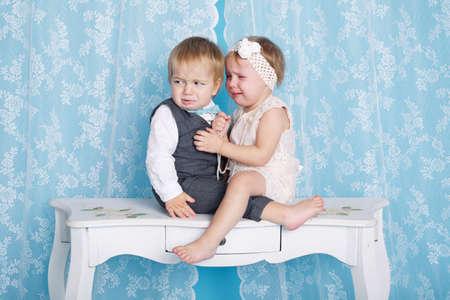 petite fille triste: mignon petit gar�on et une fille assis et pleurer avec l'autre Banque d'images