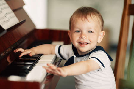 little happy boy plays piano at home Stock Photo