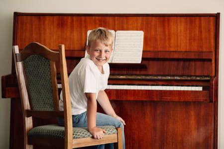 Kleine gelukkige jongen speelt piano thuis Stockfoto - 43031728