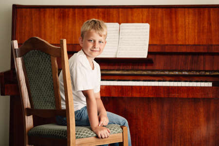 musically: little happy boy plays piano at home Stock Photo