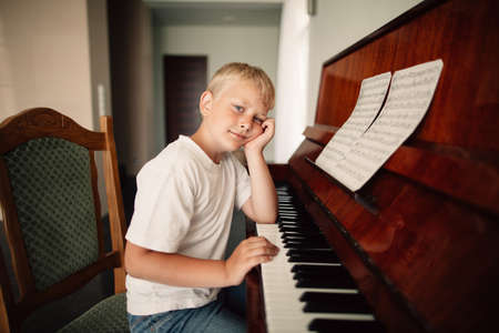 musically: little funny boy plays piano at home