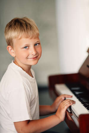 old piano: little happy boy plays piano at home Stock Photo