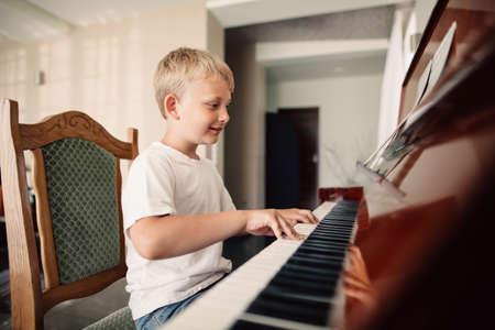 Wenig glücklich Junge spielt Klavier zu Hause Standard-Bild - 43031750