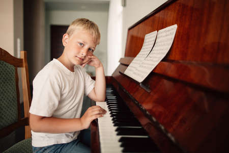 musically: little boy plays piano at home